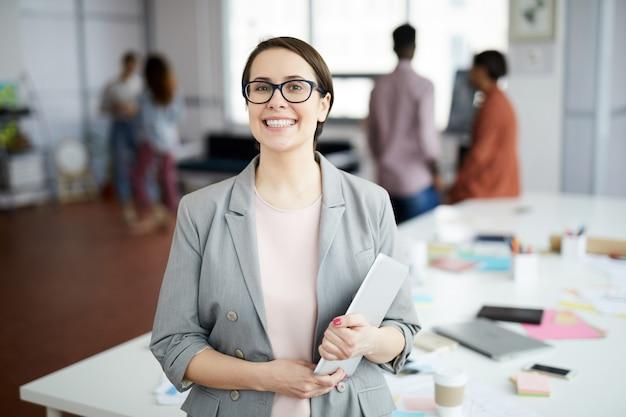 Улыбающаяся деловая женщина позирует в офисе Premium Фотографии