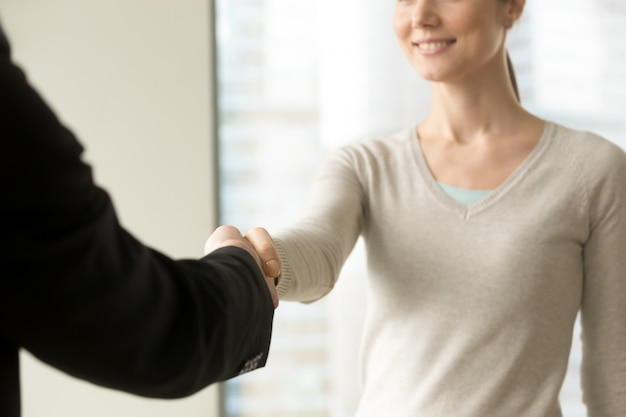 Smiling businesswoman shaking businessman hand in office Free Photo