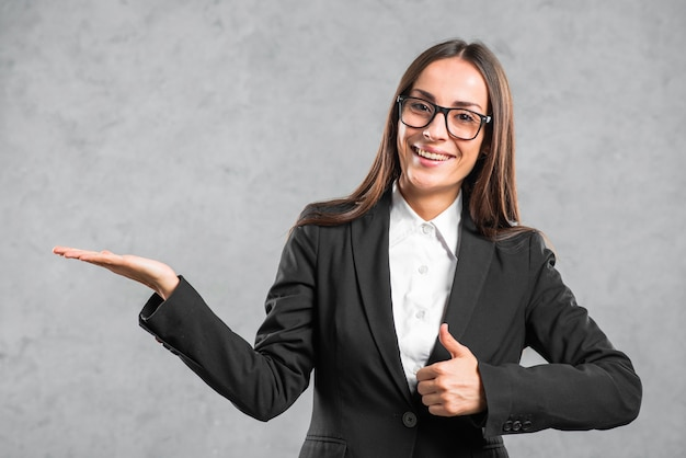 Smiling businesswoman showing thumb up sign presenting against gray background Free Photo