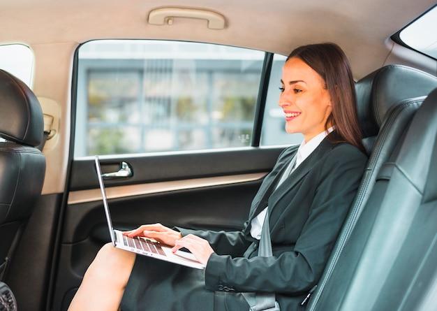 ラップトップを使用して車の中に座っている笑顔の実業家 無料写真
