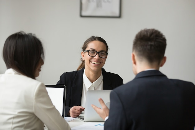 Smiling businesswoman talking with subordinated about reports Free Photo