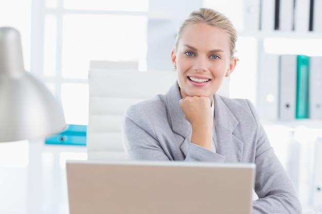 Smiling businesswoman using her computer Premium Photo