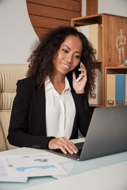 Smiling businesswoman with phone and laptop Free Photo