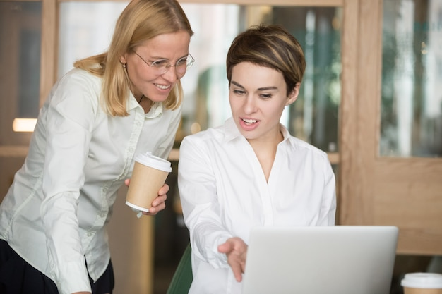 Smiling businesswomen discussing good online project result looking at laptop Free Photo