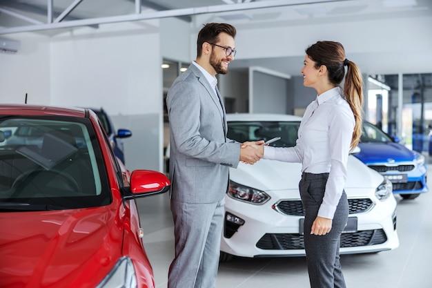 車を購入したいブルネットと握手する笑顔の車の売り手。カーサロンのインテリア。周りには多くの異なる現代の車があります。 Premium写真