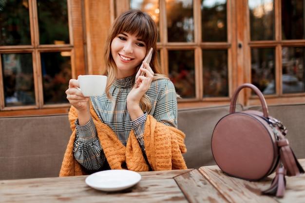 Sorridente donna spensierata ha una pausa caffè in un accogliente bar con interni in legno, utilizzando il telefono cellulare. tenendo la tazza di cappuccino caldo. stagione invernale. Foto Gratuite