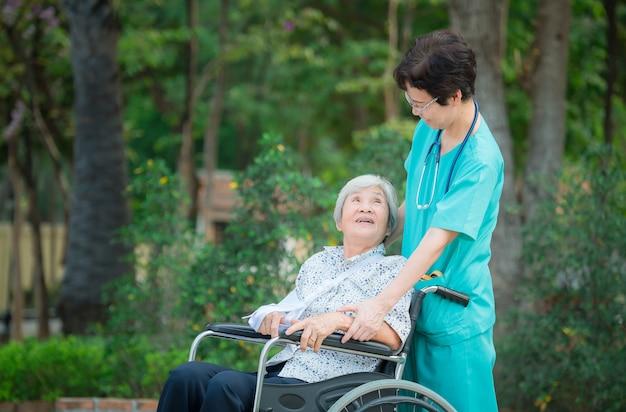 Smiling caregiver senior nurse take care a senior patient on wheelchair Premium Photo