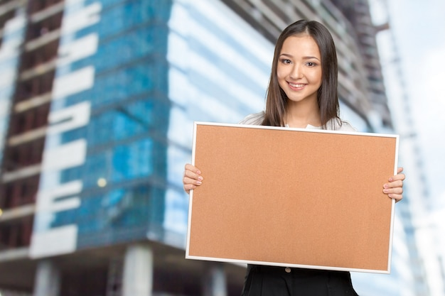 Smiling casual woman holding the empty corkboard Premium Photo