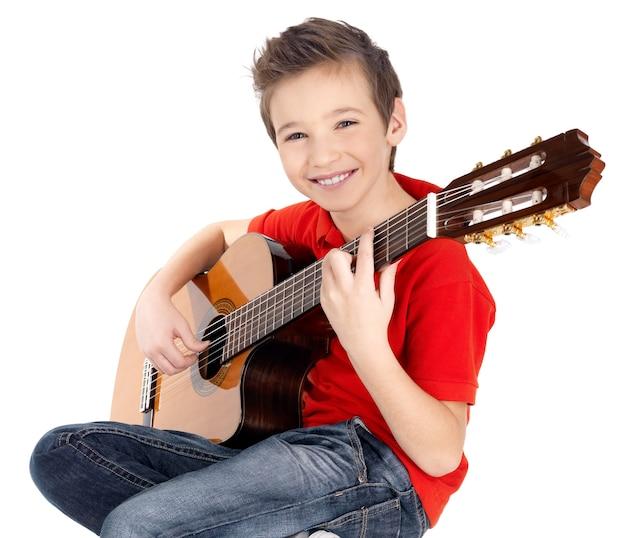 Улыбающийся кавказский мальчик играет на акустической гитаре - Бесплатные Фотографии