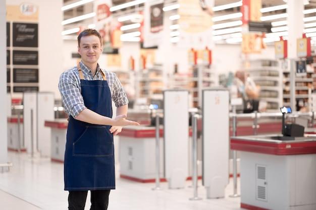 Smiling caucasian salesman invites to store with a gesture Premium Photo