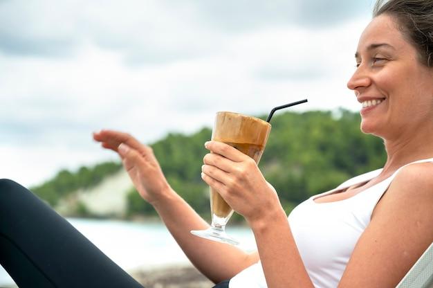 泡と丘のあるビーチでコーヒードリンクを保持し、わらを飲む白人女性 無料写真