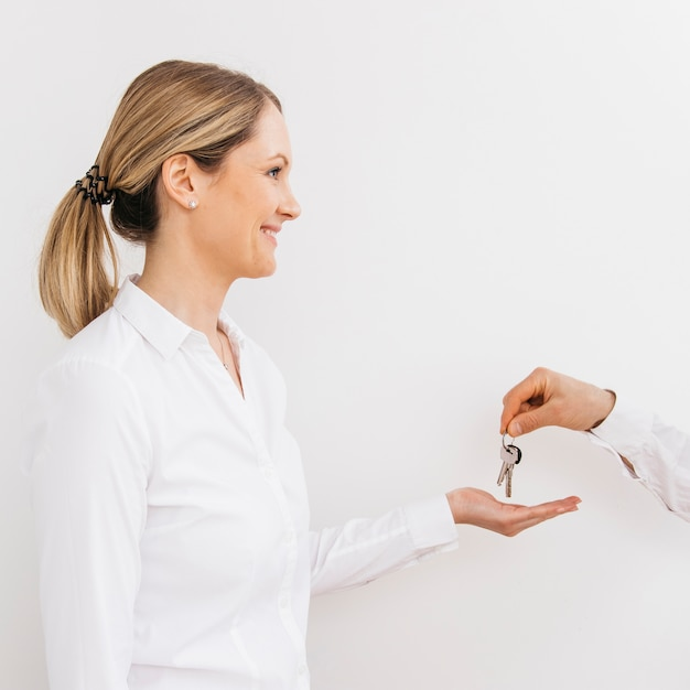 Smiling caucasian woman receiving keys from man Free Photo