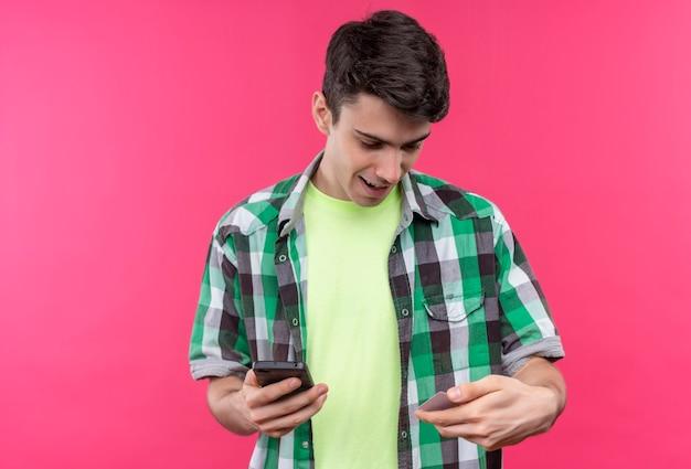 電話を保持し、孤立したピンクの背景に彼の手でクレジットカードを探して緑のシャツを着て笑顔の白人の若い男 無料写真