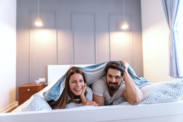 ベッドの中で胃の上に横たわるとシートでカバーしている陽気な白人カップルの笑顔 Premium写真