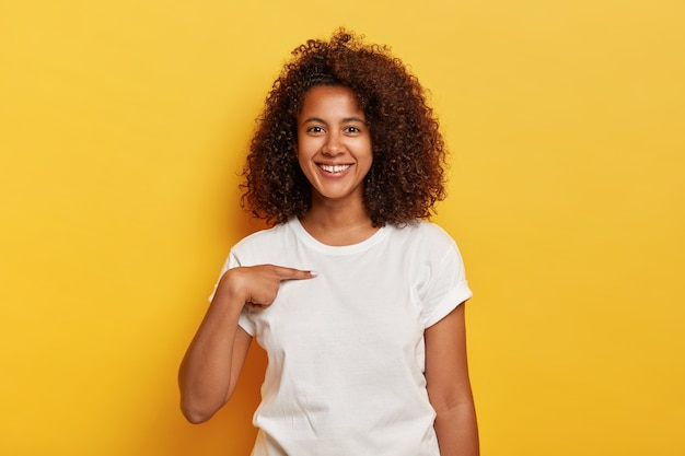 Smiling cheerful dark skinned girl points at herself, shows mockup space on white t shirt, happy being picked, models against yellow wall. carefree delighted young afro woman asks who me Free Photo