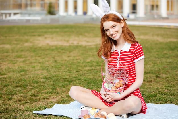 Улыбающаяся жизнерадостная женщина с длинными рыжими волосами в ушах зайчика Бесплатные Фотографии