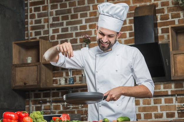 Smiling chef standing in kitchen sprinkling spices on frying pan Free Photo