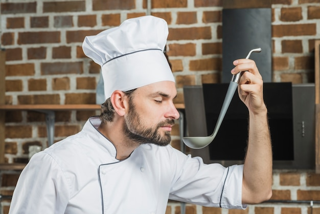 Smiling chef with eyes closed smelling the soup in kitchen Free Photo