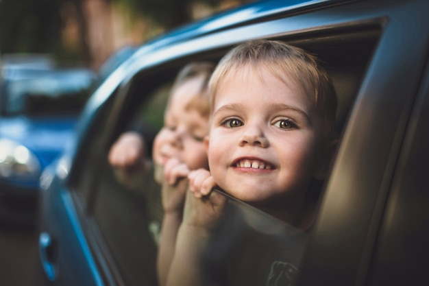 Smiling child looking out of a car window Premium Photo