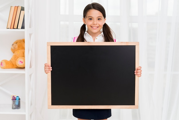 Smiling child in school uniform showing blackboard in classroom Free Photo