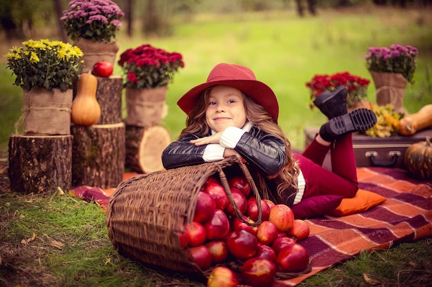 Smiling child with basket of red apples sitting in autumn park Premium Photo