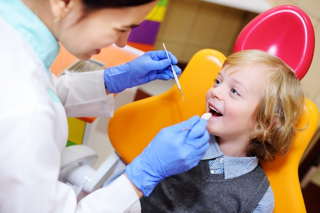 Smiling child with light curly hair on examination in the dental chair Premium Photo