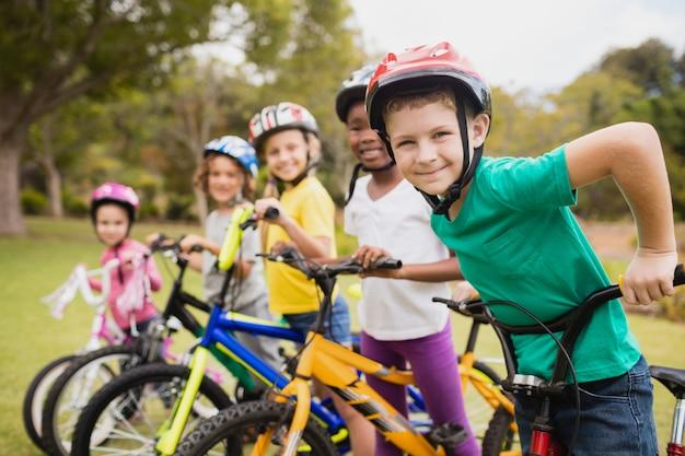 Smiling Children Posing In Raw With Bikes Premium Photo