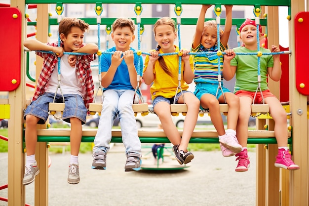 Smiling classmates sitting in a row on the playground Free Photo