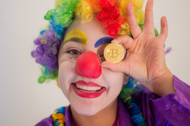 Smiling clown holding a bitcoin coin in the direction of his eyes Premium Photo