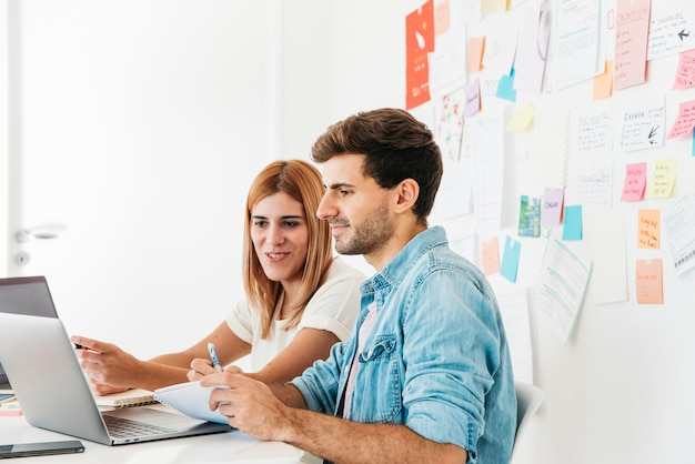 Smiling colleagues looking at laptop at workplace Free Photo