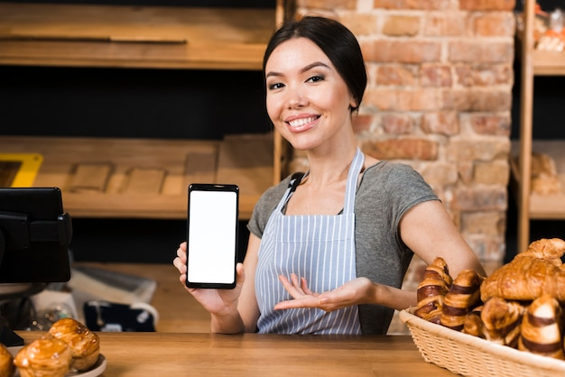 Smiling confident female baker at the bakery counter showing mobile phone display Free Photo