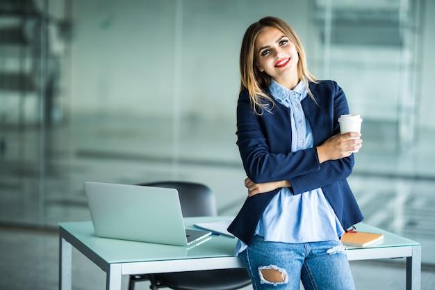 Sorridente fiduciosa giovane donna d'affari con i capelli ricci in piedi alla scrivania comune e guardando mentre beve il caffè in ufficio open space Foto Gratuite