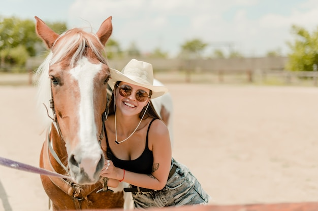 Smiling country girl in cowboy hat with her horse on a ranch Premium Photo