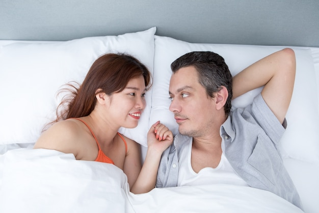 Smiling Couple Chatting and Lying in Bed Free Photo
