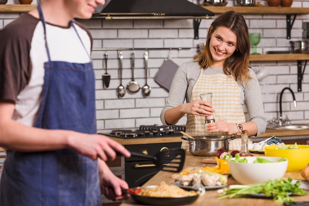 Smiling couple cooking dishes together Free Photo