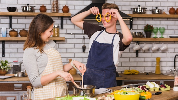 Smiling couple cooking and playing with vegetables in kitchen Free Photo