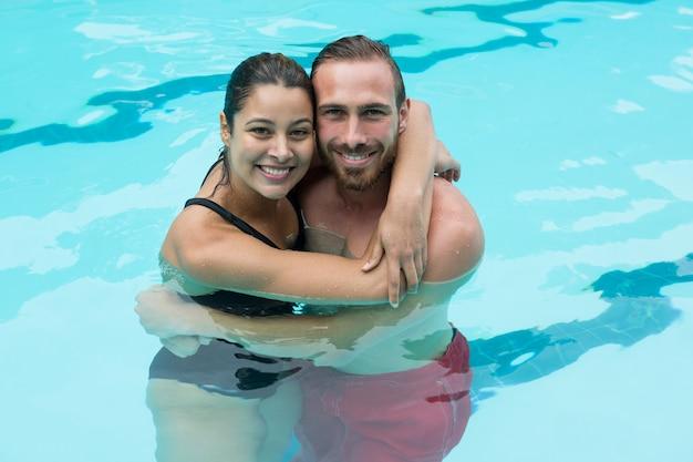スイミングプールを受け入れる笑顔のカップル Premium写真