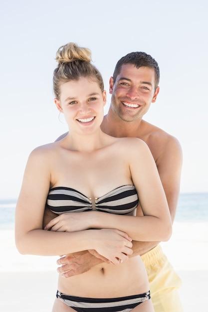 Улыбающаяся пара, обнимающаяся на пляже Premium Фотографии