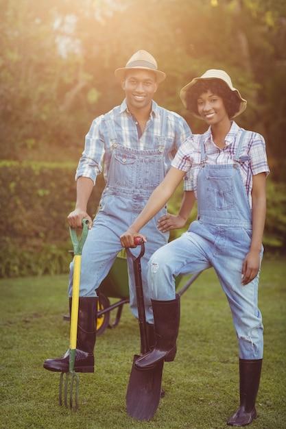 Smiling couple holding shovel and rake in the garden Premium Photo