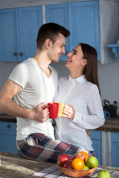 Smiling couple at kitchen looking eyes to eyes. Premium Photo