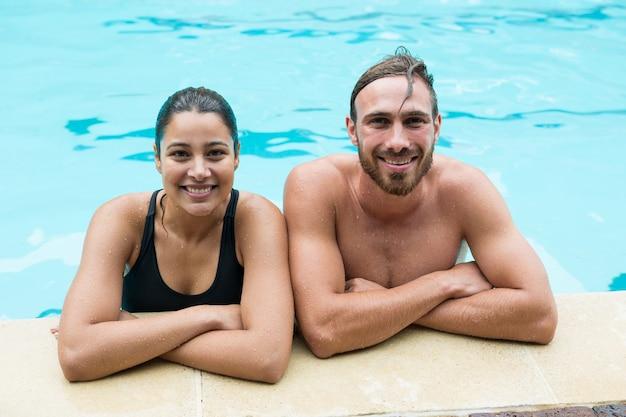 プールサイドに寄りかかって笑顔のカップル Premium写真