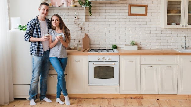 Smiling couple in love standing in kitchen Free Photo