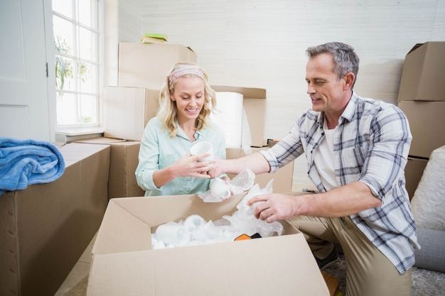 Smiling couple packing mug in a box at home Premium Photo