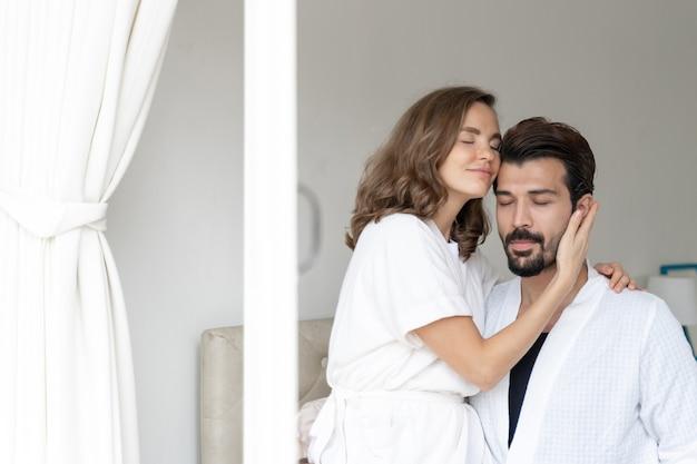 Улыбающаяся пара расслабляется и обнимаются в постели Бесплатные Фотографии