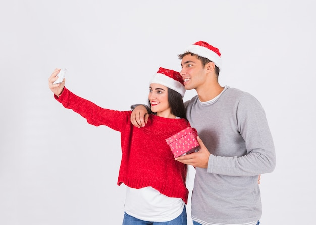 Smiling couple taking selfie with gift  Free Photo