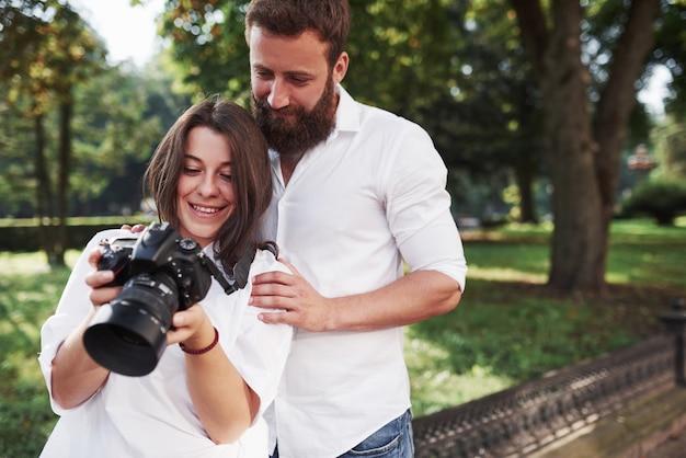カメラで写真を見て笑顔のカップル。 無料写真
