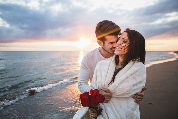 Smiling couple walking on the beach with a bouquet of roses at sunset Free Photo