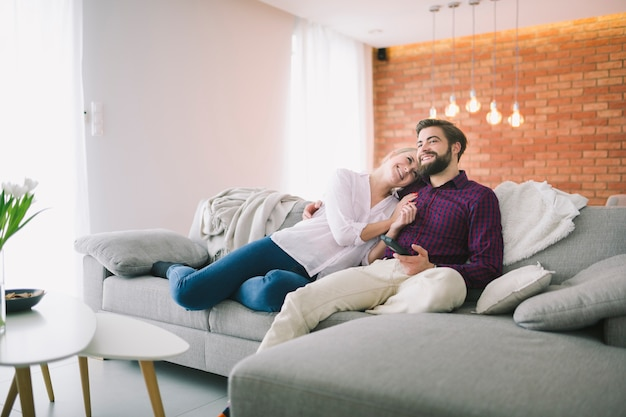 Smiling couple watching tv at home Free Photo