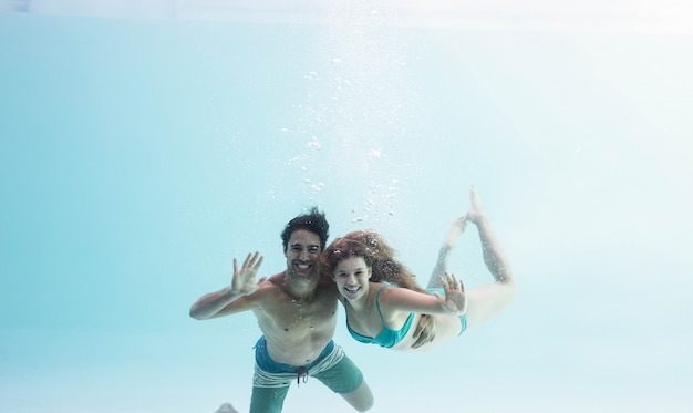 Smiling couple under water cheering Premium Photo