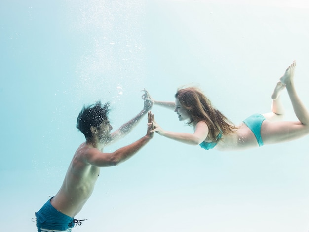Smiling couple under water putting hands together Premium Photo